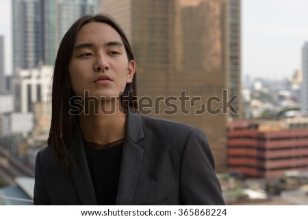 Asian businessman with long hairstyle outdoors
