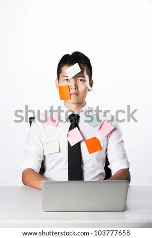 Asian businessman with post-it notes on his face and body.