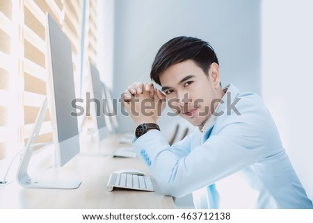 Asian businessman working at computer In office and looking camera