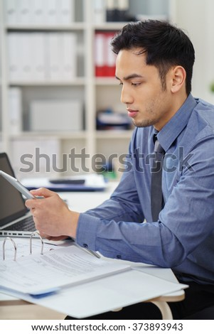 Asian businessman working at his desk in the office reading information on a tablet, computer with a serious expression