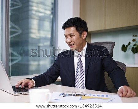 asian businessman working on laptop in office. - stock photo