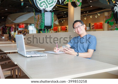 Asian Businessman working with smartphone and laptop in canteen. - stock photo