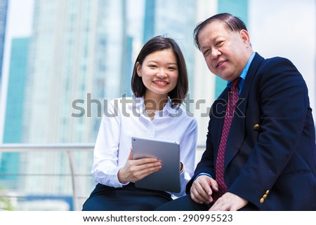 Asian businessman & young female executive using tablet