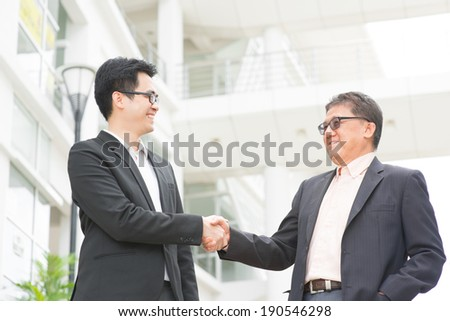 Asian businessmen handshaking. Senior CEO hand shake with young executive. Modern  office building architecture background. - stock photo