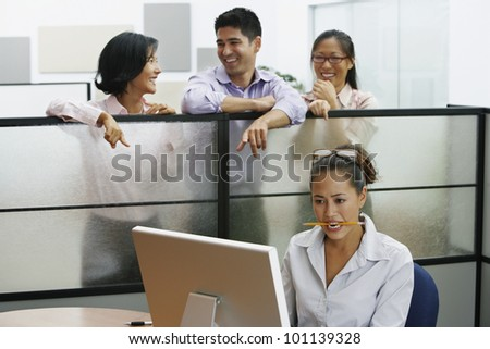 Asian businesspeople pointing at businesswoman - stock photo