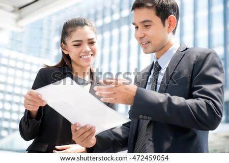 Asian businesswoman and businessman standing and discussing document outdoor