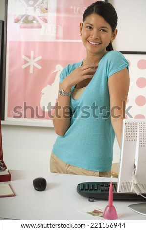 Asian businesswoman behind desk - stock photo