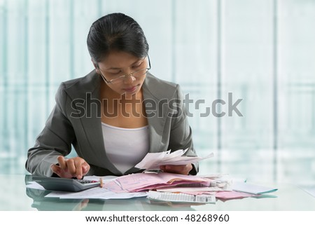 Asian businesswoman calculating pile of bills in the office - stock photo