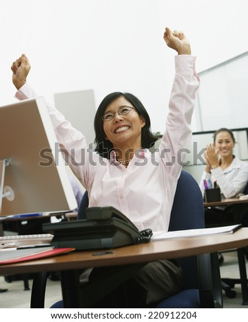 Asian businesswoman cheering at desk