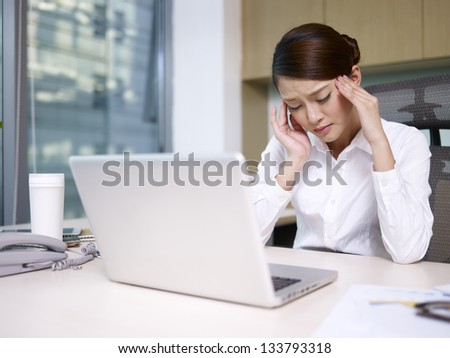 asian businesswoman having a headache in office. - stock photo