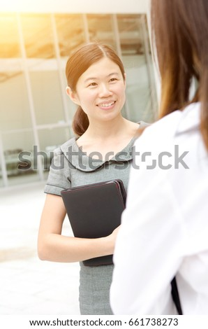 Asian businesswoman having conversation, office building as background
