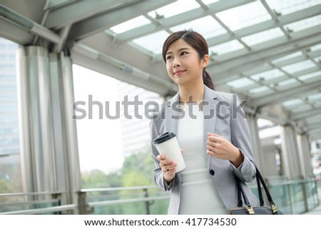 Asian Businesswoman holding a coffee and walking outdoor - stock photo