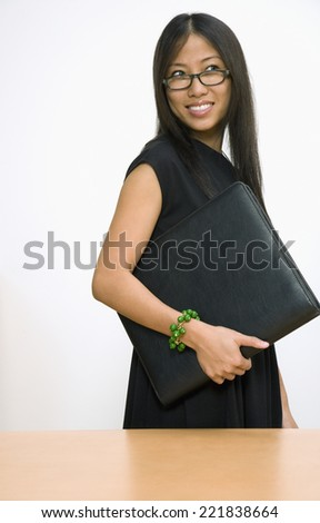 Asian businesswoman holding portfolio - stock photo
