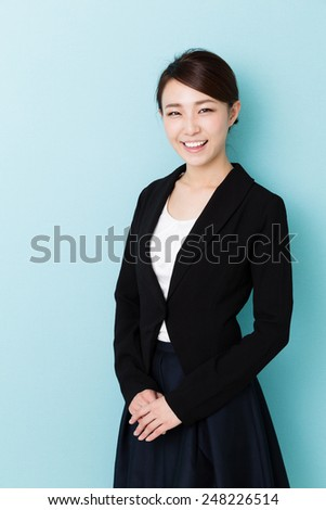 asian businesswoman isolated on blue background - stock photo
