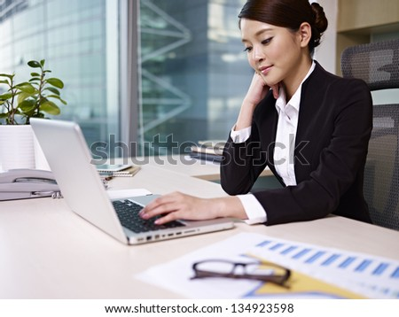 asian businesswoman looking at laptop computer in office.