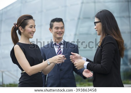 Asian Businesswoman presenting her business card to a female business collegue.  - stock photo