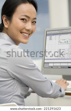 Asian businesswoman typing on computer