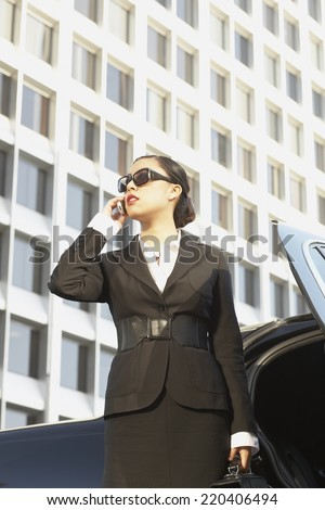 Asian businesswoman using cell phone next to car - stock photo