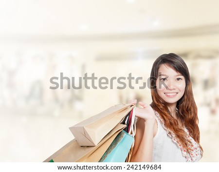 Asian businesswoman with long hair hold shopping bag sale has shopping mall background.Mixed Asian / Caucasian businesswoman. - stock photo