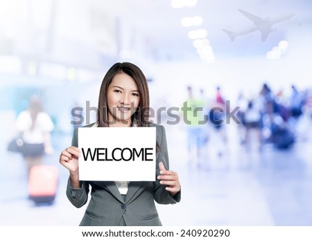 Asian businesswoman with long hair holding a sign board with a welcome has airport background.Mixed Asian / Caucasian businesswoman. - stock photo