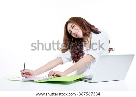 Asian businesswoman working in office, looking tired. - stock photo