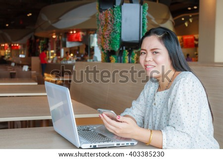 Asian Businesswoman working with smartphone and laptop in canteen. - stock photo