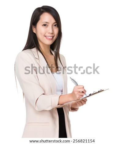 Asian businesswoman write on folder - stock photo
