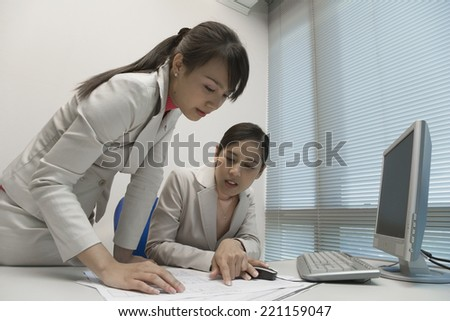 Asian businesswomen looking at paperwork