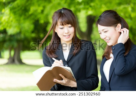 asian businesswomen working in the park - stock photo
