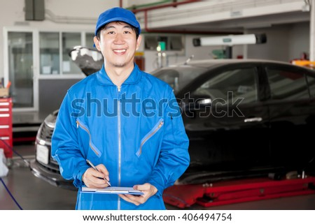 Asian car technician smiling in garage service.
