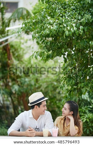Asian cheerful couple drinking cocktails and chatting