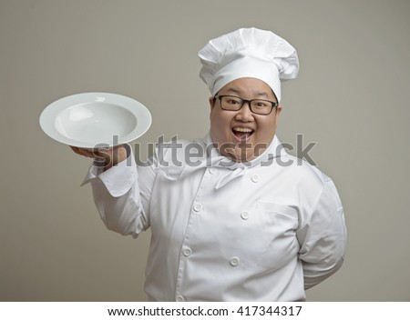 Asian chef holding a plate on plain background