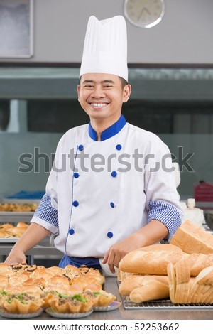 Asian chef or baker posing in front of the pastries in the commercial kitchen - stock photo