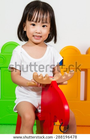 Asian Chiense girl riding trojan at indoor playground - stock photo