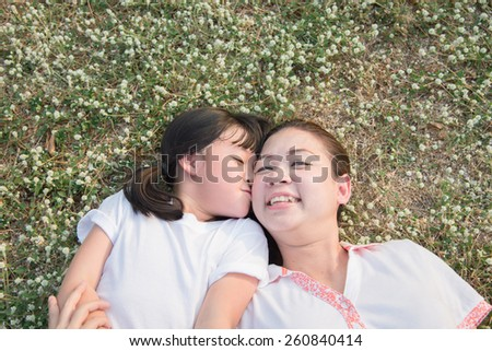Asian child and her mother laying down on the flower grass - stock photo