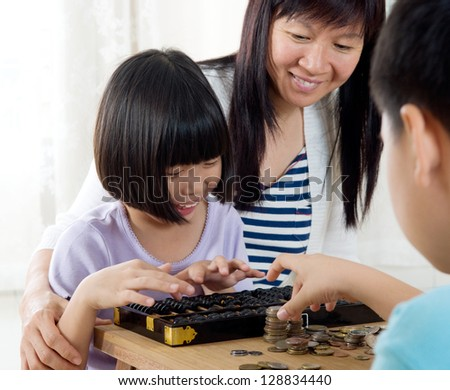 Asian child counting coins using abacus - stock photo