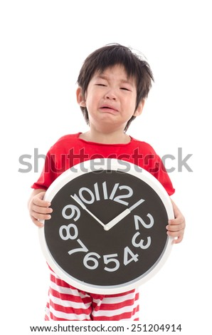 Asian child crying and holding a clock on white background isolated  - stock photo