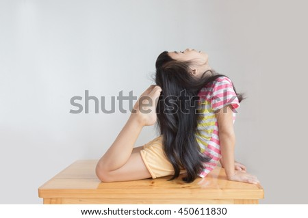 Asian Child Do Yoga In King Cobra Pose