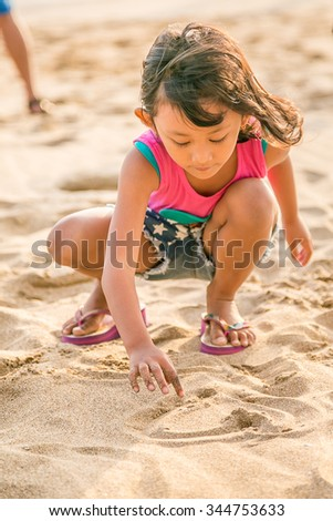 Asian Child Enjoy Writing on The White  Beach Sand, Selective Focus on Hand