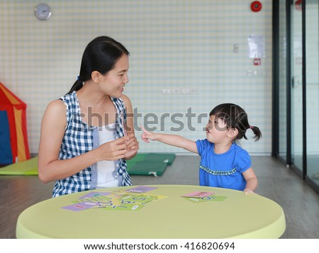 Asian Child girl and mother playing flash card for Right Brain Development at the playroom - stock photo
