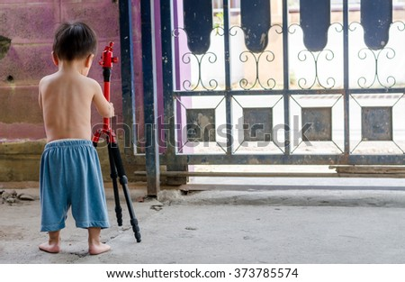 Asian child happy to play with red tripod - stock photo
