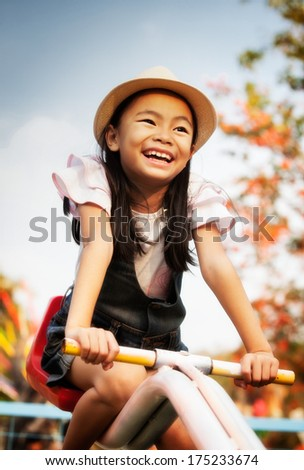 Asian child having fun on a swing - stock photo