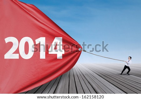 Asian child is pulling new year of 2014 to change the new future  - stock photo