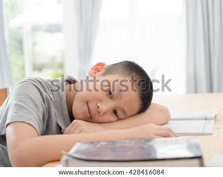 Asian child of primary school age do homework. The boy does his homework at his desk at home. The student / pupil has been bored on the lesson. Child fell asleep during homework - stock photo