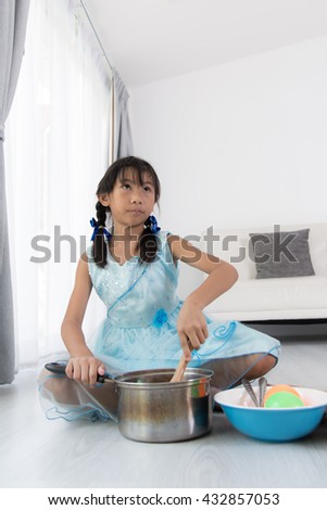 Asian child playing a chef at home.