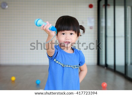 Asian Child playing plastic microphone at the kid room