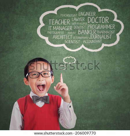 Asian child pointing at many aspirations over his head - stock photo