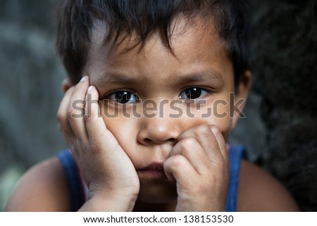 Asian child portrait - Filipino boy from impoverished area looking into camera - stock photo