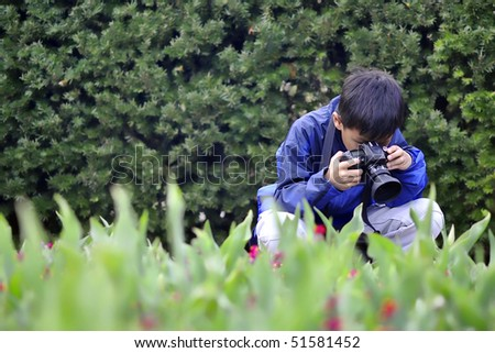 Asian Child taking a flower photo