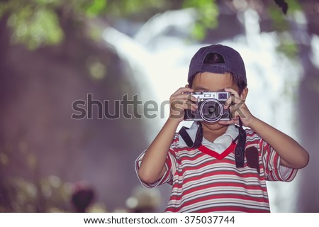 Asian child taking photo by professional digital camera on blurred waterfall background. Handsome boy in nature. Outdoors portrait. Vintage picture style. - stock photo